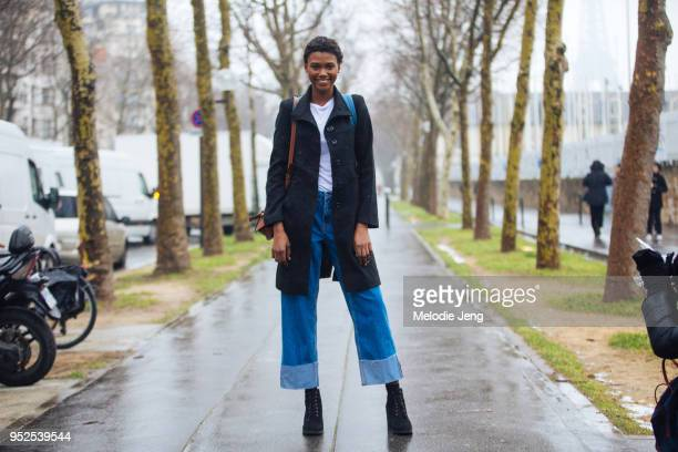 Model Ruth Akele Ayodele wears a black peacoat white tshirt widelegged jeans unhemmed cuffed jeans and black boots after the Loewe show on March 02...