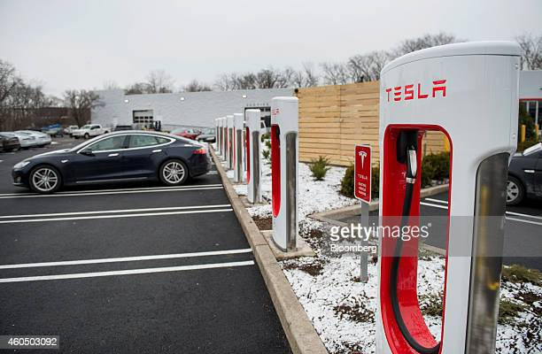 A Model S electric vehicle sits parked in front of a supercharger station stands at the Tesla Motors Inc Gallery and Service Center in Paramus New...