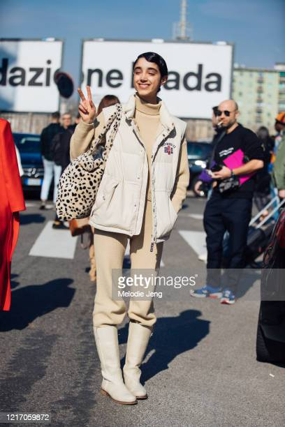 Model Saana Mirzaie throws a peace sign and wears a white River Woods vest cream sweater and pants tan boots and a leopard fuzzy bag after the MSGM...