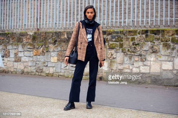 Model Sacha Quenby wears a light brown plaid blazer black headphones top pants and boots and a dark blue Loewe Balloon leather bucket bag after the...