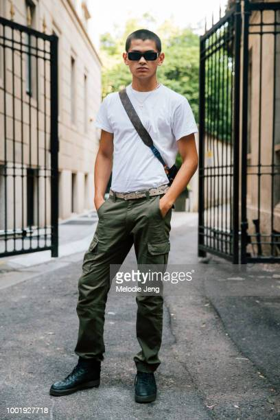 Model Sakua Kambong wears black rectangular sunglasses a white tshirt a Louis Vuitton monogram leather side bag python leather belt green cargo pants...