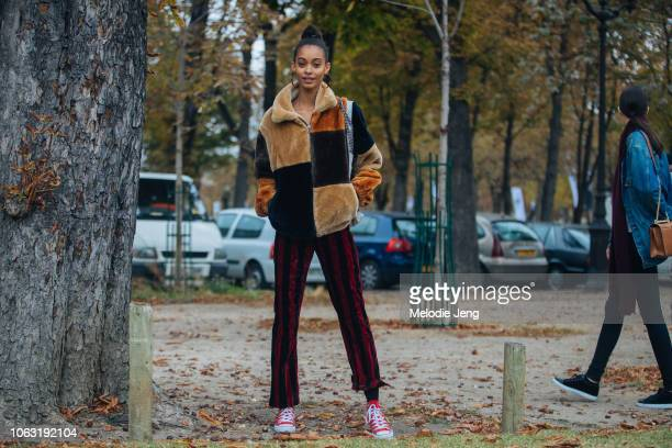 Model Samile Bermannelli wears hoop earrings a brown multicolor fur jacket red and black striped pants and red Converse sneakers during Paris Fashion...