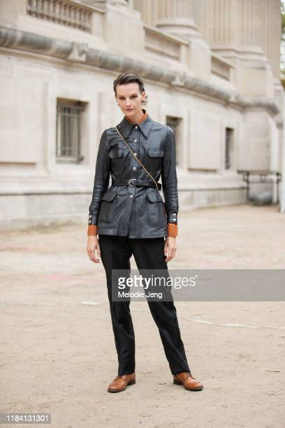 Model Sara Blomqvist wears a belted black leather jacket black trousers and brown leather brogues after the Chloé show during Paris Fashion Week...