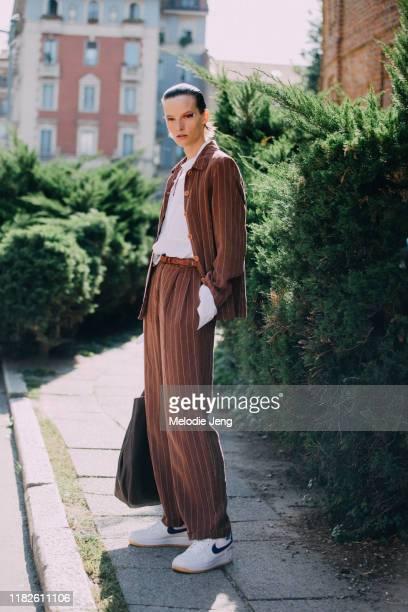 Model Sara Blomqvist wears a brown striped blazer, white top, white Nike sneakers after the Salvatore Ferragamo show during Milan Fashion Week...