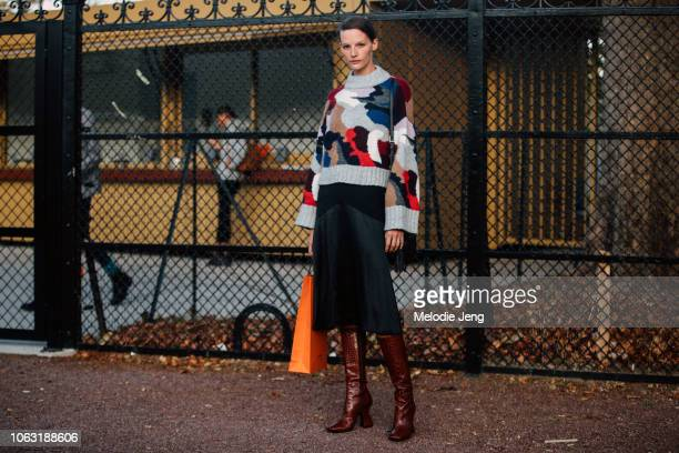 Model Sara Blomqvist wears a multicolor sweater black skirt brown leather boots after the Hermes show during Paris Fashion Week Spring/Summer 2019 on...