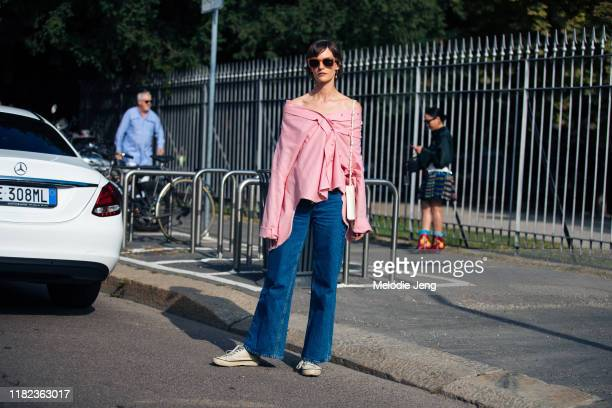Model Sara Blomqvist wears a pink off-shoulder assymetrical top, blue jeans, and white sneakers after the Tod's show during Milan Fashion Week...