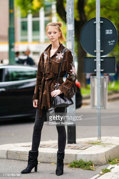 Model Sara Grace Wallerstedt wears a brown suede fringed jacket with printed flowers a black leather bag black leggings black boots outside the Fendi...