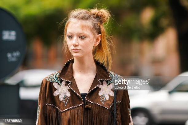 Model Sara Grace Wallerstedt wears a brown suede fringed jacket with printed flowers outside the Fendi show during Milan Fashion Week Spring/Summer...