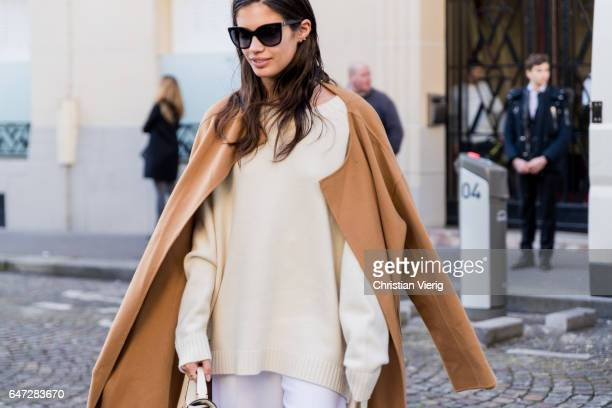 Model Sara Sampaio wearing a brown wool coat beige knut white flared pants outside Balmain on March 2 2017 in Paris France