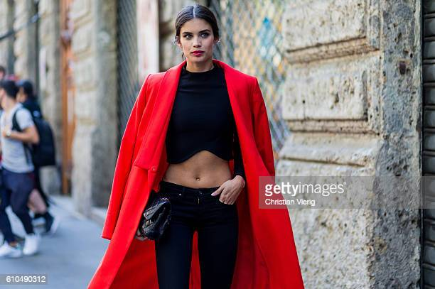 Model Sara Sampaio wearing a red coat and black cropped top outside Dolce Gabbana during Milan Fashion Week Spring/Summer 2017 on September 25 2016...