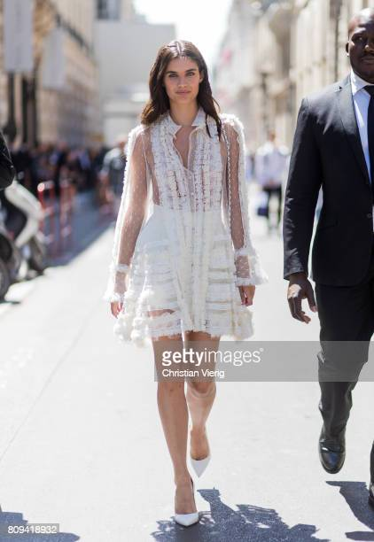 Model Sara Sampaio wearing a white sheer ruffled dress white Chanel bag outside Elie Saab during Paris Fashion Week Haute Couture Fall/Winter...