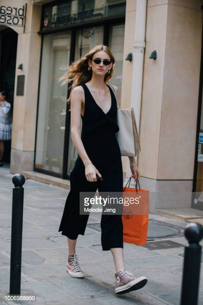 Model Sarah Berger wears a black jumpsuit and pink Converse sneakers after the Hermes resort show during Couture Fall/Winter 2018 Fashion Week on...