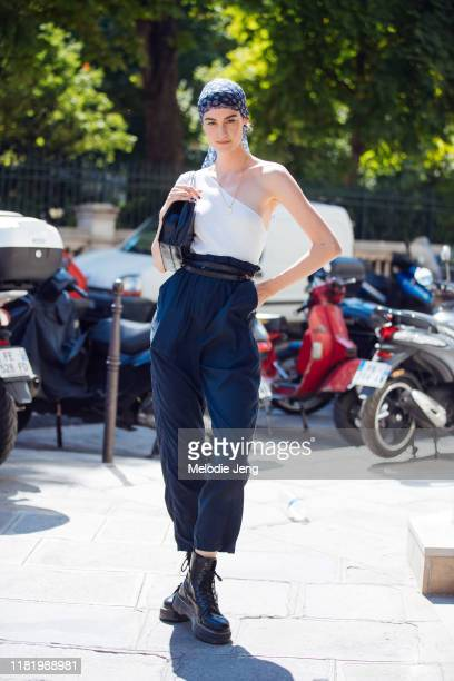 Model Sarah Boursin wears a blue headscarp, white single shoulder top, blue high-waisted pants with a belt, and black boots after the Jean Paul...