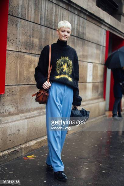 Model Sarah Fraser wears a black sweater small Loewe rust color Gate bag and loose blue trousers on March 04 2018 in Paris France