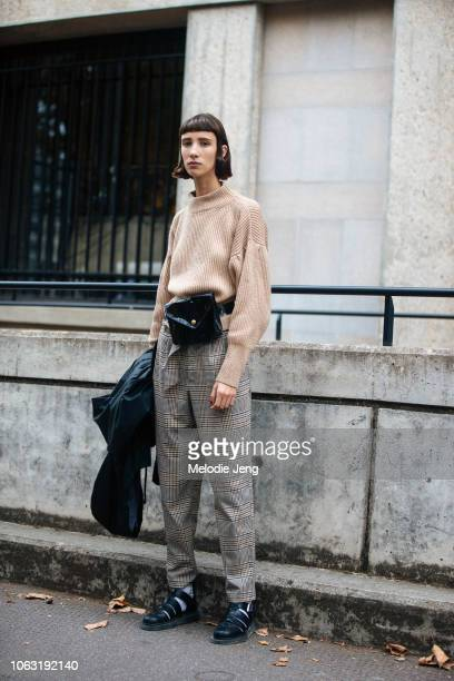 Model Sasha Knysh wears a light brown sweater black beltbag gray plaid pants and black sandals with socks after the Miu Miu show during Paris Fashion...