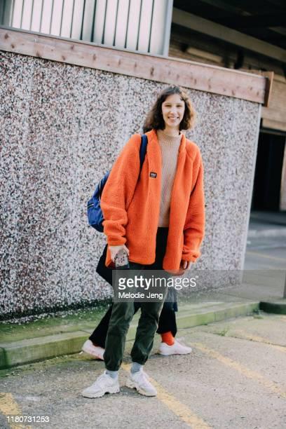 Model Sasha Knysh wears an orange Helly Hansen fleece jacket, green pants, and white sneakers after Preen by Thornton Bregazzi during London Fashion...
