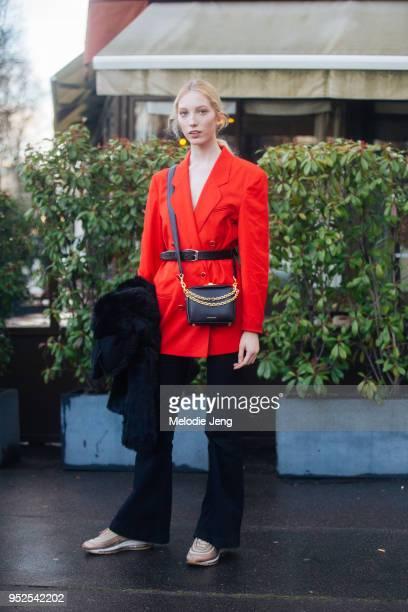 Model Sasha Komarova wears a red blazer a black Alexander McQueen bag with a chain black flared pants and metallic rose gold Air Max Ultra 97...