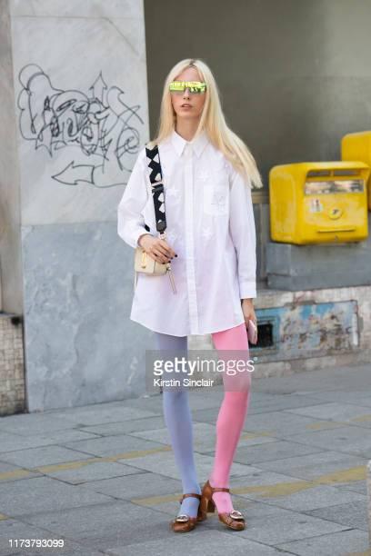 Model Sasha Komarova wears Miu Miu shoes Aeria sunglasses Marc Jacobs bag a white shirt dress with embroidered stars and Calzedonia tights on July 03...