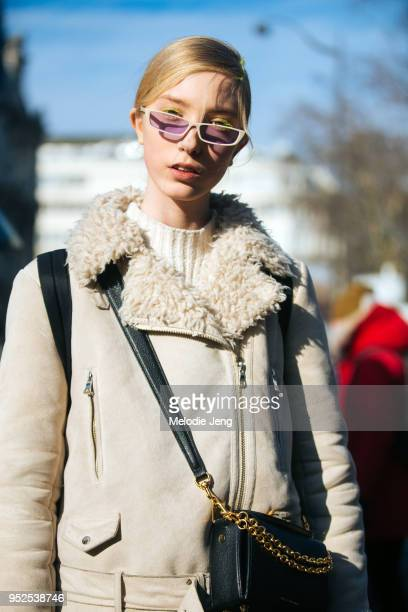 Model Sasha Komarova white and purpletinted slim sunglasses a cream bomber jacket with a shearling collar and a crossbody black Alexander McQueen box...