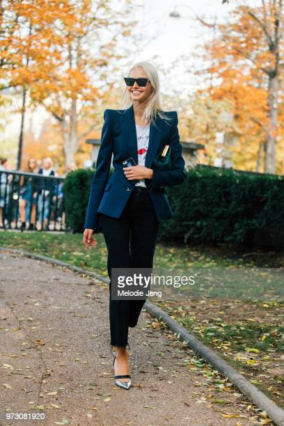 Model Sasha Luss attends a show and wears a dark blue blazer with high shoulders black pants and silver heels during Paris Fashion Week Spring/Summer...