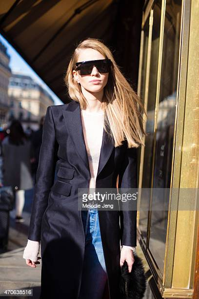 Model Sasha Luss exits the Balmain show in Karl Lagerfeld sunglasses and a DSquared2 coat at the Grand Hotel on Day 3 of Paris Fashion Week FW15 on...