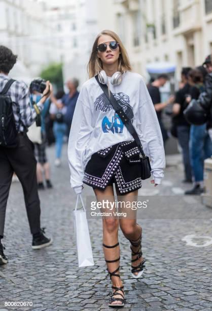 Model Sasha Luss wearing gladiator sandals white long shirt mini skirt outside Balmain during Paris Fashion Week Menswear Spring/Summer 2018 Day Four...