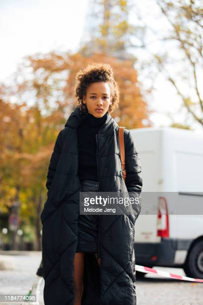 Model Sculy Mejia wears a black sleeping bag black puffer down jacket after the Miu Miu show during Paris Fashion Week Spring/Summer 2020 on October...