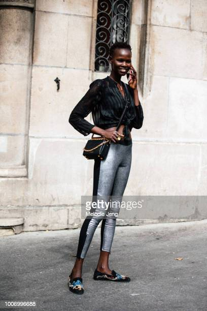 Model Shanelle Nyasiase talks on the phone and wears a black shirt tied at the chest black Mcqueen purse silver leggings and embellished felt...
