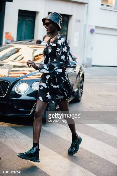 Model Shanelle Nyasiase wears a black bucket hat, black and white print dress, black Calvin Klein socks, and black boots. After the Valentino show...