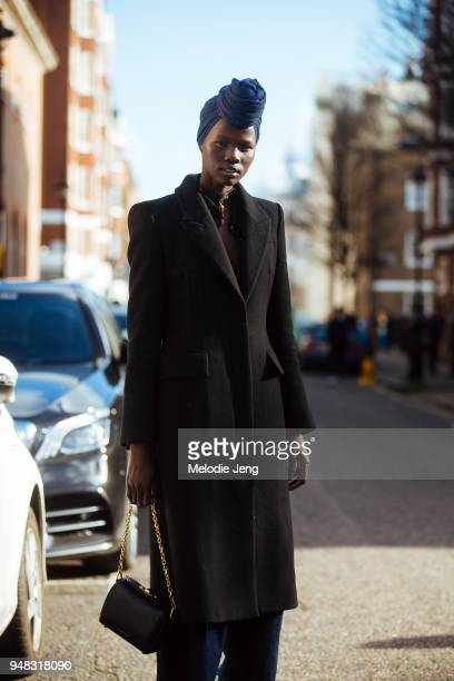 Model Shanelle Nyasiase wears a blue hair turban a marblestyle necklace a long black coat and an Alexander McQueen black box bag during London...