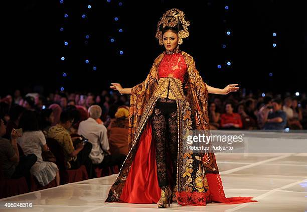 A model showcases designs by Anne Avantie at the Merenda Kasih show during her 25th anniversary as a fashion designer at Pakuwon Imperial Ballroom on...