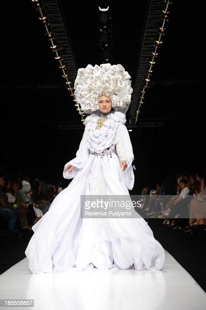 A model showcases designs by Fenny Mustafa on the runway at the Queen of Scarf show during Jakarta Fashion Week 2014 at Senayan City on October 22...