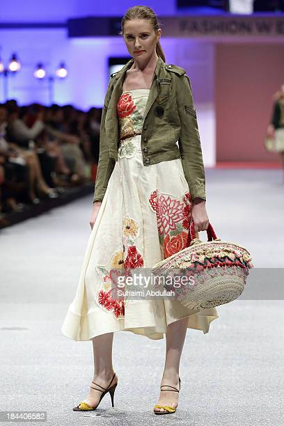 A model showcases designs by Keita Maruyama on the catwalk on day 5 of Fashion Week 2013 at the Sands Expo Convention Centre on October 13 2013 in...