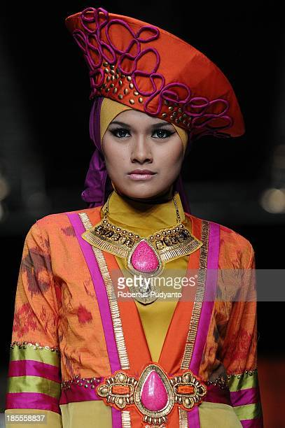 A model showcases designs by Lia Afif on the runway at the Cymaversa Queen show during Jakarta Fashion Week 2014 at Senayan City on October 22 2013...