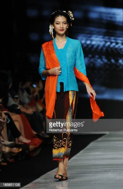 A model showcases designs by Obin on the runway at the Indonesia Memanggil show during Jakarta Fashion Week 2014 at Senayan City on October 25 2013...
