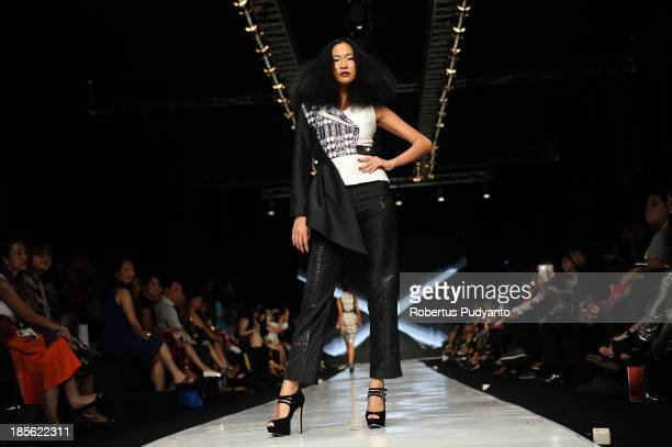 A model showcases designs by Peggy Hartato and hair by Nick Malenko on the runway at the It Looks Fall Winter 13/14 show during Jakarta Fashion Week...