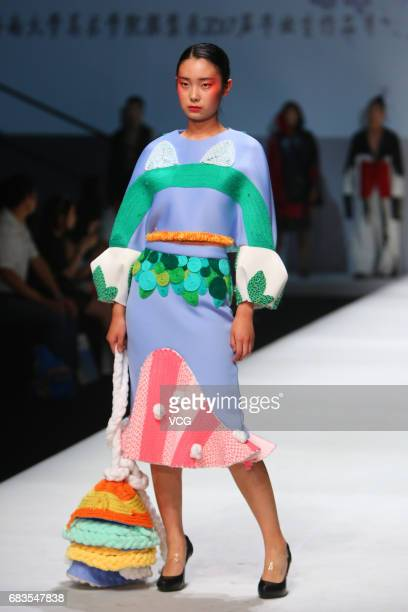 Model showcases designs designed by graduates of College of Fine Arts of University of Jinan on the runway during day one of China Graduate Fashion...
