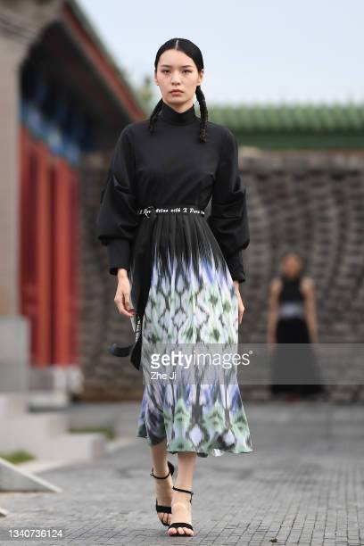Model showcases designs during the SILUNISHANG & PURE TOUCH collection show on day two of 2021 Beijing Fashion Week at Longfu Cultural Center on...