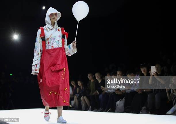 Model showcases designs on runway at Changzhou Vocational Institute Of Textile And Garment show during China International College Student Fashion...