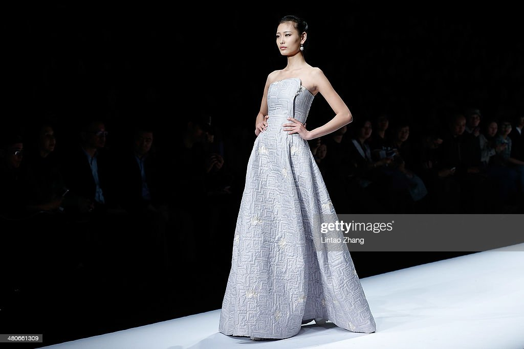 A model showcases designs on the catwalk during the LIANVIS Lian Huiqing Collection show of Mercedes-Benz China Fashion Week Autumn/Winter 2014/2015 at the 751D-PARK Workshop on March 26, 2014 in Beijing, China.