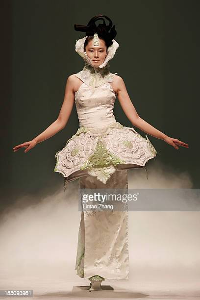 A model showcases designs on the catwalk during the XuMing Haute Couture Collection of the China Fashion Week S/S Collection 2013 at Beijing Hotel on...