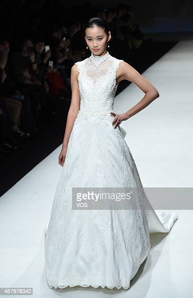 A model showcases designs on the runway at AOLISHA Wei Xinkun Bridal Wear Collection show during the third day of the MercedesBenz China Fashion Week...