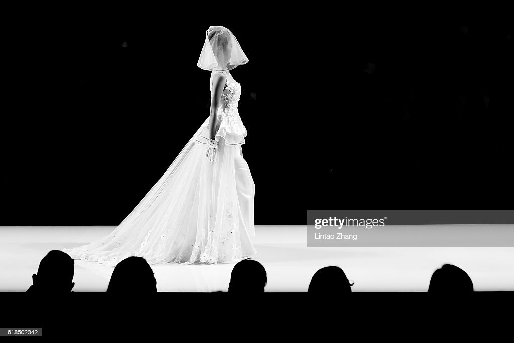 A model showcases designs on the runway at Cai Meiyue wedding dress conference show during Mercedes-Benz China Fashion Week Spring/Summer 2017 at Beijing Hotel on October 27, 2016 in Beijing, China. The fashion week runs from 25 October to 02 November.