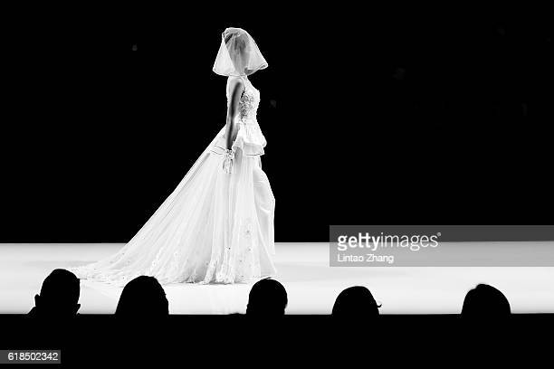 Model showcases designs on the runway at Cai Meiyue wedding dress conference show during Mercedes-Benz China Fashion Week Spring/Summer 2017 at...