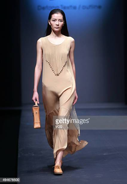 A model showcases designs on the runway at DEFANG TEXTILE/OUTLINE Collection during the MercedesBenz China Fashion Week Spring/Summer 2016 at...