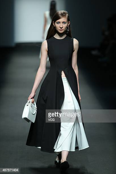 A model showcases designs on the runway at Haotian Wen collection show during the third day of the Shanghai Fashion Week 2015 Spring/Summer at...