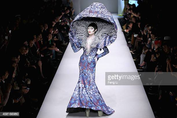 A model showcases designs on the runway at Hu Sheguang Collection show during MercedesBenz China Fashion Week Spring/Summer 2015 at Beijing Hotel on...