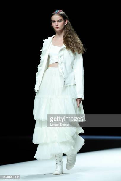 A model showcases designs on the runway at the MX Collection show by designer Yang Shan during the MercedesBenz China Fashion Week Spring/Summer 2018...