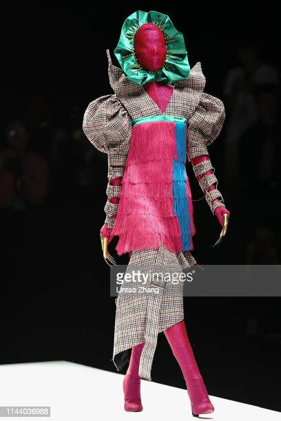 Model showcases designs on the runway at the 'School of Innovation Design, Guangzhou Academy of Fine Arts' show on day four of China International...