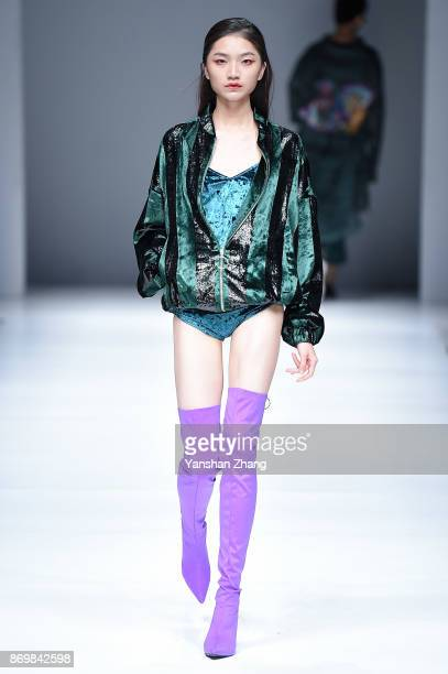 A model showcases designs on the runway at the YÕS mono fashion show by designer Liang Yan during the MercedesBenz China Fashion Week Spring/Summer...